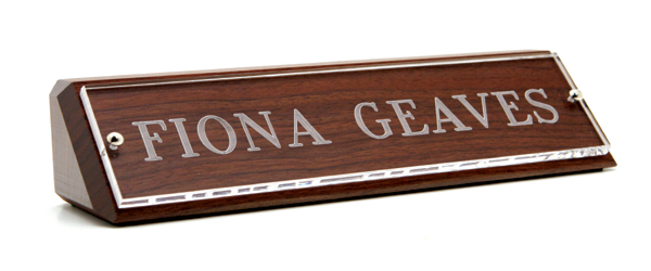 Engraved nameplates are made of Lucite mounted onto a block of solid wood.