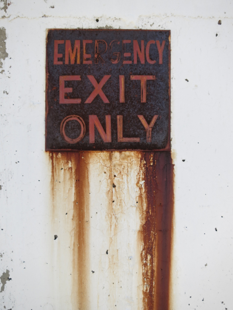 Emergency exit signs should be much more visible than this one. From Paul Sableman.